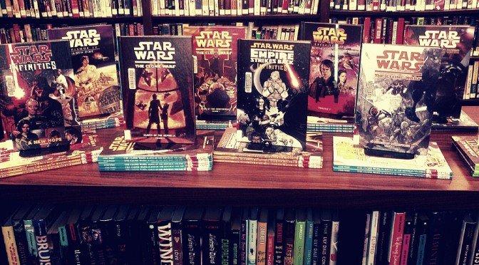 """a photo of an enormous collection of new """"Star Wars"""" graphic novels displayed on the top of a book shelf island in the YA section at the library"""