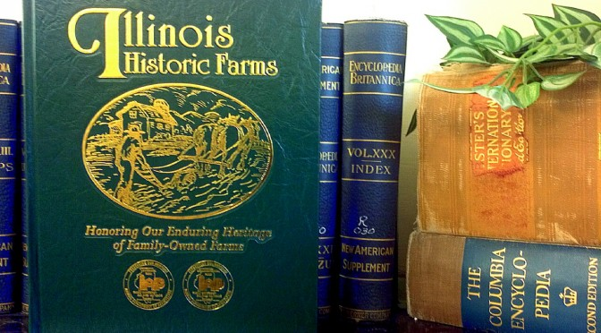 """Photo of the recently added book """"Illinois Historic Farms: Honoring Our Enduring Heritage of Family-Owned Farms"""" shown setting atop a bookcase in front of several encyclopedias"""