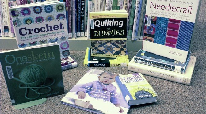 A picture of many hobby books displayedon the floor of the library in front of a bookshelf. Subjects include knitting, crocheting, and other needlework.