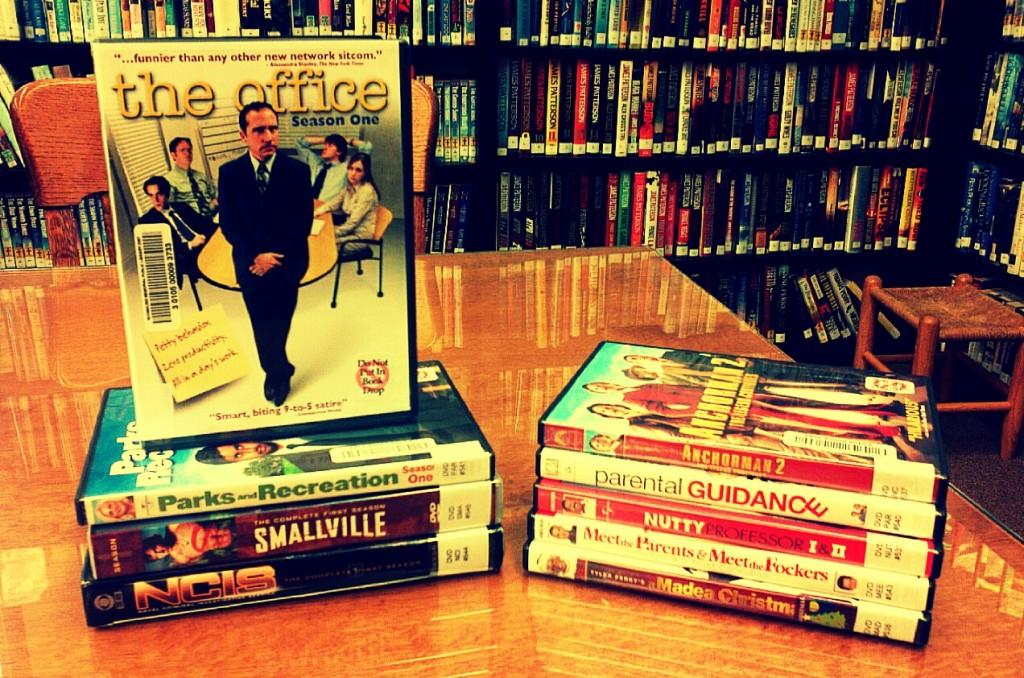 "picture of many new DVDs stacked up on a library table; ""The Office: Season One"" is featured"