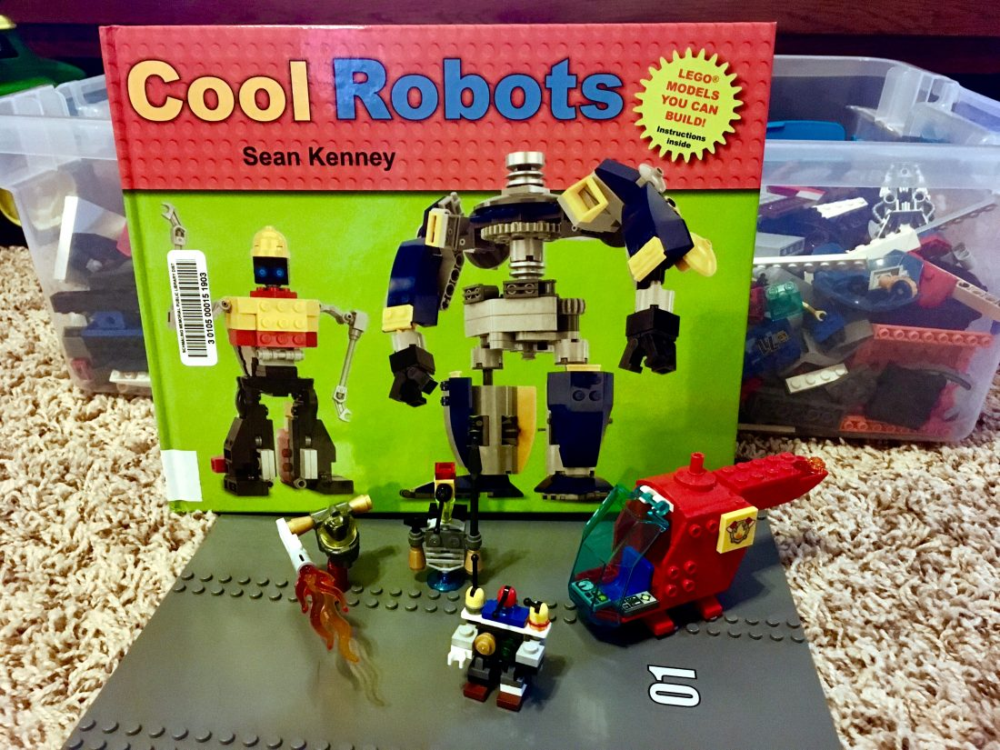 photo of a lego building book with several lego robots standing in front of it