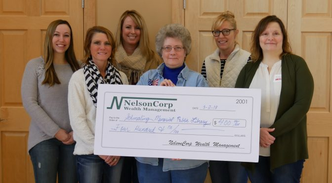 A photo of NelsonCorp Wealth Management team members donating a check to Gwenn Smith of Schmaling Memorial Library.