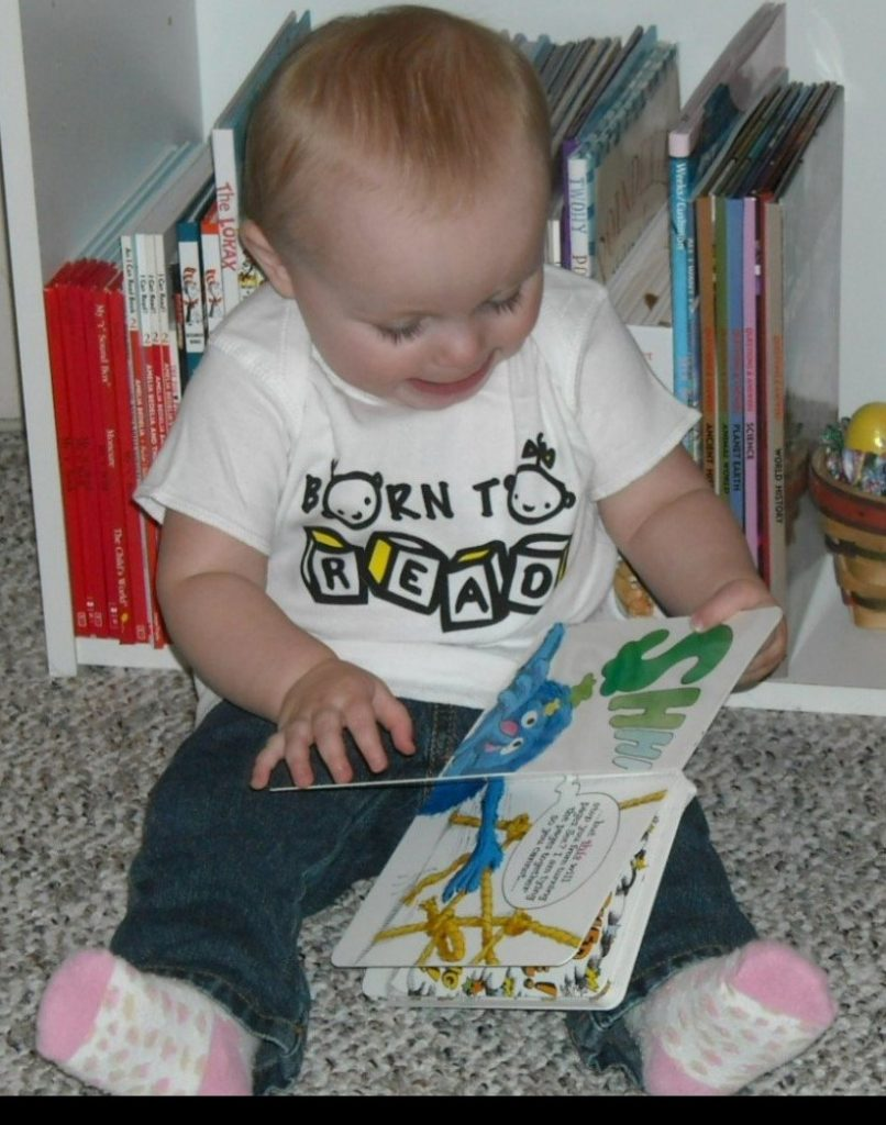 Photo of baby reading a book