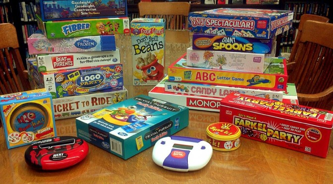 A photograph of numerous new family and children's board games stacked and sprawled out on the library table.